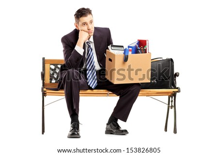 Disappointed redundant businessman in a suit sitting on a bench with a box of belongings isolated on white background