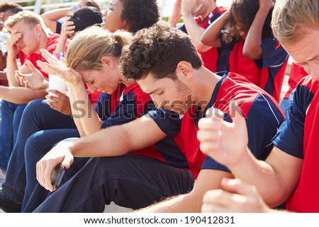 Disappointed Spectators In Team Colors Watching Sports Event - stock photo