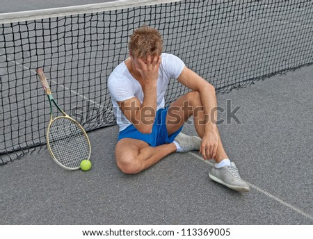 Disappointed tennis player, sitting on the ground, holding his head.