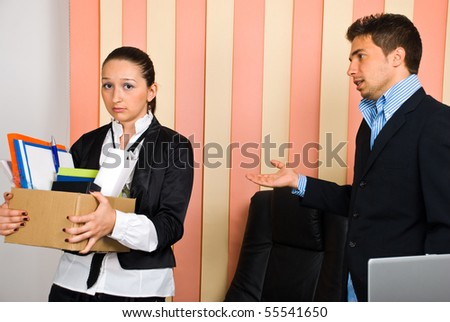 Disappointed woman  holding box with  belongings is fired by her boss and invited to leave the office - stock photo