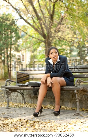 disappointed young afro businesswoman sitting in park - stock photo