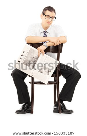 Disappointed young businessperson sitting on a wooden chair and holding a newspaper isolated against white background - stock photo