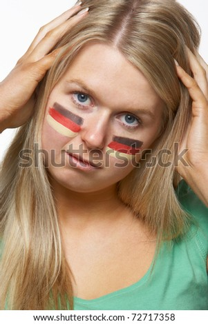 Disappointed Young Female Sports Fan With German Flag Painted On Face - stock photo