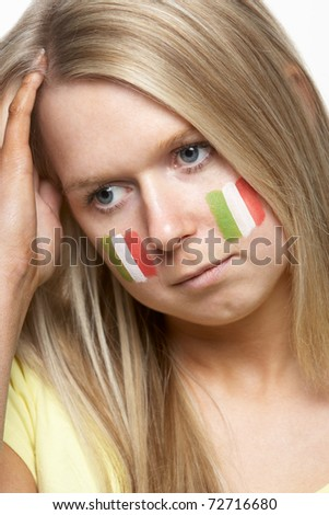 Disappointed Young Female Sports Fan With Italian Flag Painted On Face - stock photo