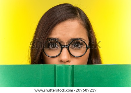 Disappointed young girl with nerd glasses. beautiful woman holding open book - stock photo