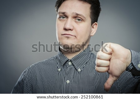 disappointed young man showing thumb down sign - stock photo