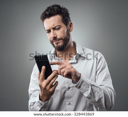 Disappointed young man typing on his touch screen smartphone