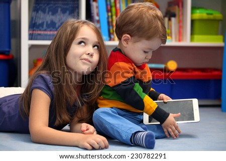 Disappointing girl with her little brother using a digital tablet computer - stock photo