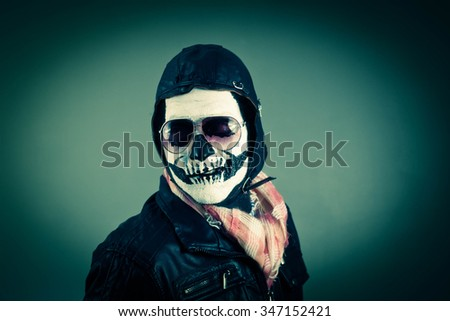 Disapproving aviator with face painted as human skull - stock photo