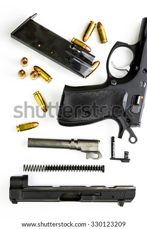 Disassembled handgun on white background, top view - stock photo