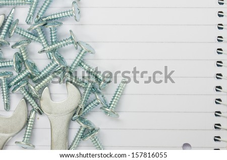 disassembled screws and wrenches on ruled paper background with yellow tape an copy space - stock photo