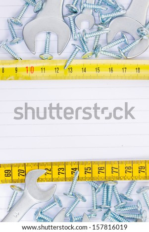 disassembled screws and wrenches  workshop background with yellow tape an copy space - stock photo