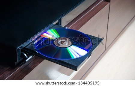 Disc insterted to DVD or CD player - stock photo
