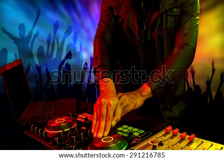 Disc jockey mixer turntable with crowd dance in nightclub at party - stock photo
