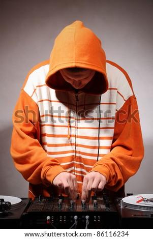 Disc jockey playing hip-hop music on professional top-class club equipment - stock photo