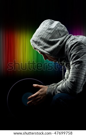 Disc jockey preparing for concert.Disc jockey holding a long playing record against colorful background - stock photo