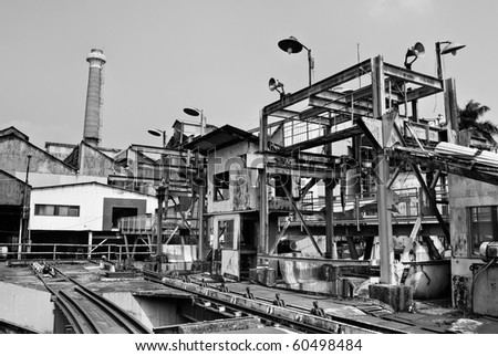 Discard old industrial factory exterior with buildings and smokestack. - stock photo