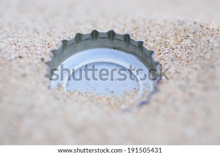 Discarded bottle cap laying on a beach. - stock photo