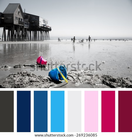 Discarded children's buckets on Old Orchard Beach, Maine, USA. Faded effect photo with selective colour highlighting the buckets. In a colour palette with complimentary colour swatches. - stock photo