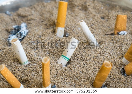 Discarded Cigarette in outdoors ashtray with sand closeup - stock photo