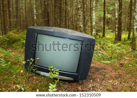 Discarded television set in the forest - stock photo