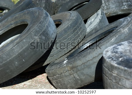 Discarded worn-out automobile tires. - stock photo