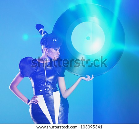 Disco african women stands with big vinyl record in her hand and neon light - stock photo