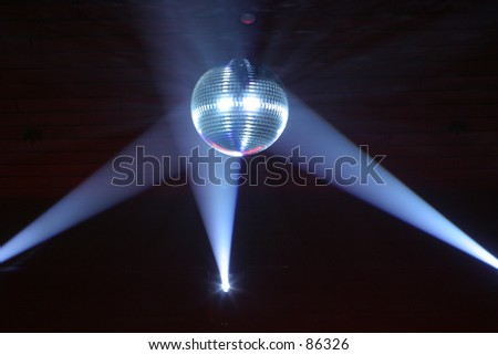 Disco ball at a nightclub lit by spotlights. - stock photo