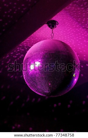 Disco ball in motion reflecting pink light in night music club with copy-space - stock photo