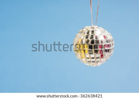 Disco mirror ball on blue background with copyspace. Concept of nightlife, clubbing and party. - stock photo