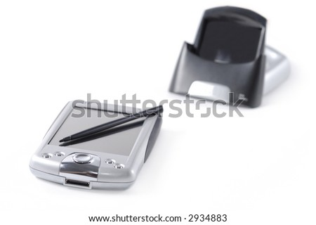 Disconnected pocket pc, cradle and stylus isolated over white background