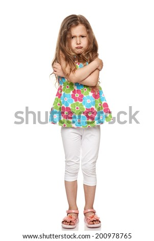 Discontent little girl standing in full length over white background - stock photo