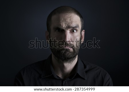 Discontented man feeling pressurized indicating how tight the terms are, isolated on black background. - stock photo