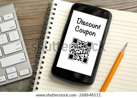 discount coupon qr code on mobile phone, with desk background - stock photo