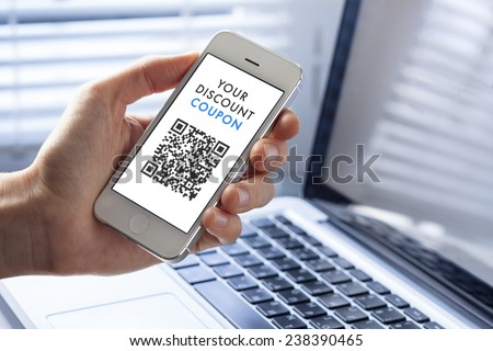 Discount coupon with QR code on smartphone with laptop in background - stock photo