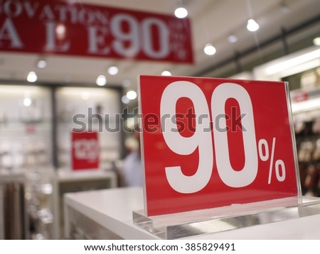 Discount signs in shop window, big reductions,with blur sales store in background. - stock photo