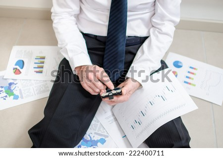 Discouraged businessman sitting on the floor using his smartphone