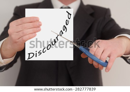 Discouraged, man in suit cutting text on paper with scissors