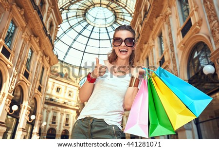 Discover most unexpected trends in Milan. Portrait of happy fashion woman in eyeglasses with colorful shopping bags in Galleria Vittorio Emanuele II showing thumbs up - stock photo