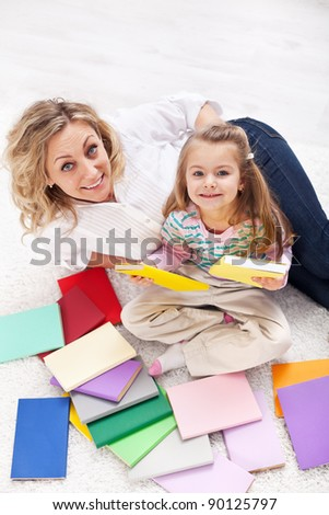 Discovering the world of books - little girl and woman laying on the floor - stock photo