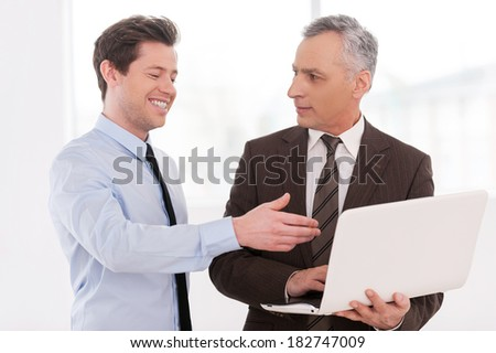 Discussing a new project. Two cheerful business men discussing something while one of them holding laptop