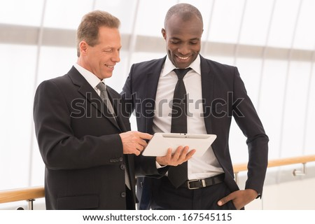 Discussing a new project. Two cheerful business men looking at the digital tablet and smiling - stock photo