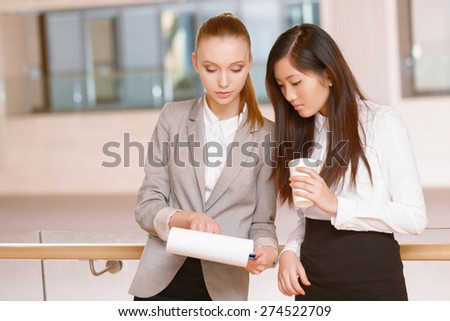 Discussing a plan. Young businesswoman holding a folder and her colleague drinking coffee having a talk - stock photo