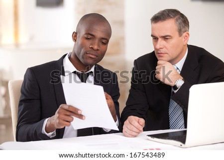 Discussing a project. Two confident business people in formalwear discussing something while one of them pointing a paper - stock photo