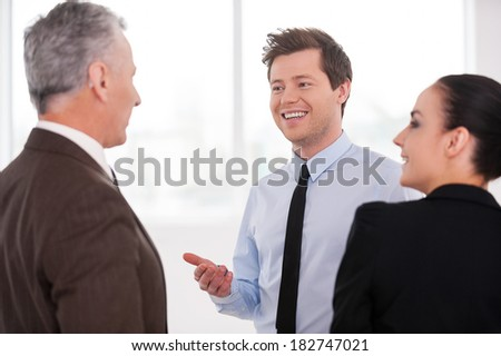 Discussing a successful project. Three cheerful business people discussing something while standing close to each other - stock photo