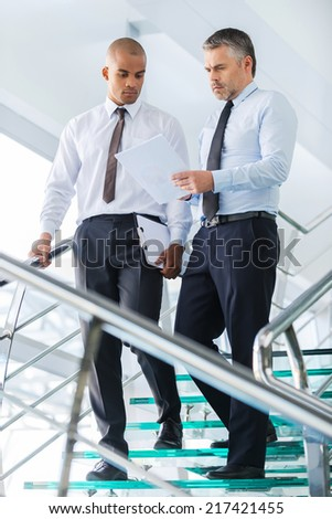 Discussing business contract. Two confident businessmen discussing something and looking at paper while moving down by staircase  - stock photo