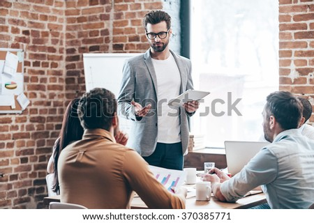Discussing business issues. Young handsome man holding digital tablet and discussing something while his coworkers listening to him sitting at the office table - stock photo