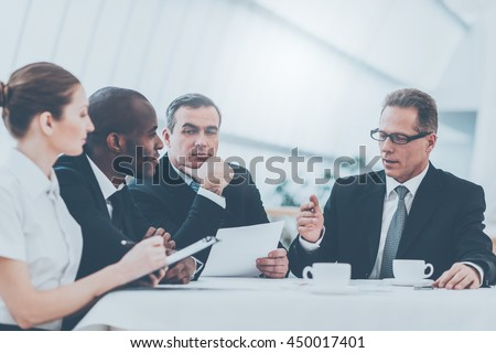 Discussing business together. Business people in formalwear discussing something while sitting together at the table - stock photo