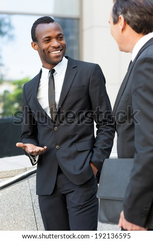 Discussing business. Two cheerful business men talking and gesturing while standing outdoors