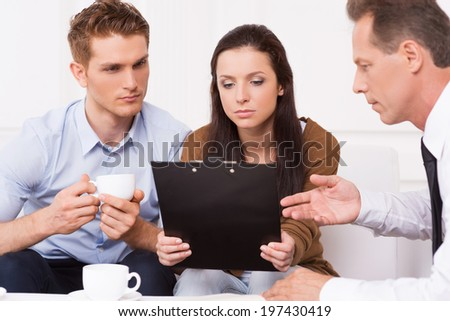 Discussing contract conditions. Thoughtful young couple sitting on the couch while mature man in formalwear explaining something and pointing clipboard - stock photo
